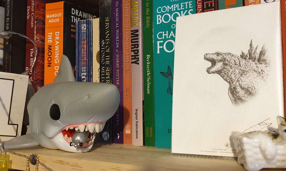 A bookshelf with a Funko Pop of Jaws next to a drawing of Godzilla