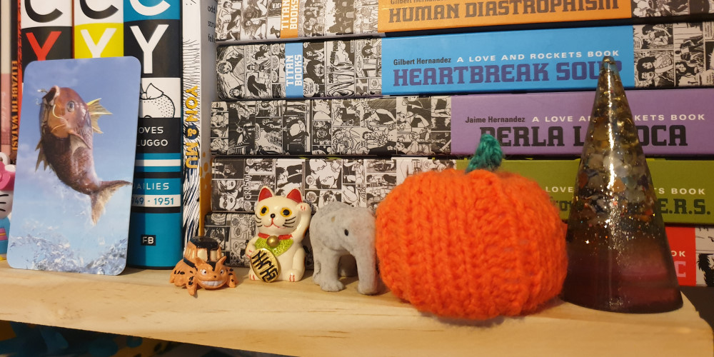 A shelf with graphic novels. In front of the books is a card with a magikarp on it, a small toy catbus, a small lucky cat, a small elephant, a knitted pumpkin, and a cone made from resin with glitter and rocks in it.