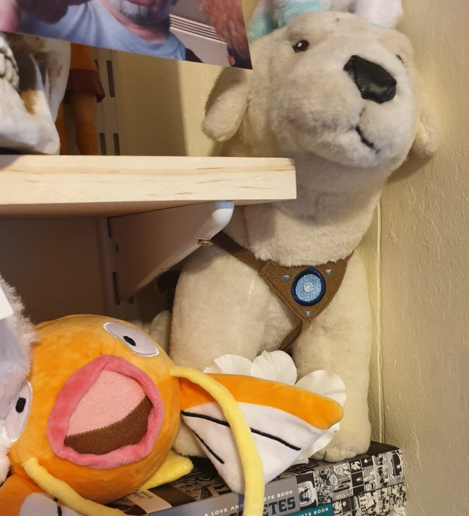 A stuffed toy Naga and a stuffed toy Magikarp tucked between shelves