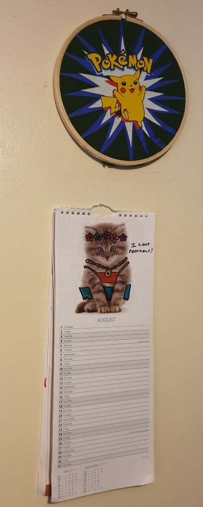 A picture in an embroidery hoop and a calendar hanging on a wall