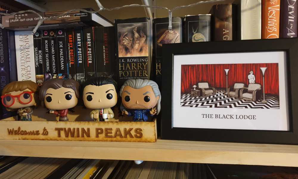 Four Twin Peaks Funko Pops next to a picture of the Black Lodge
