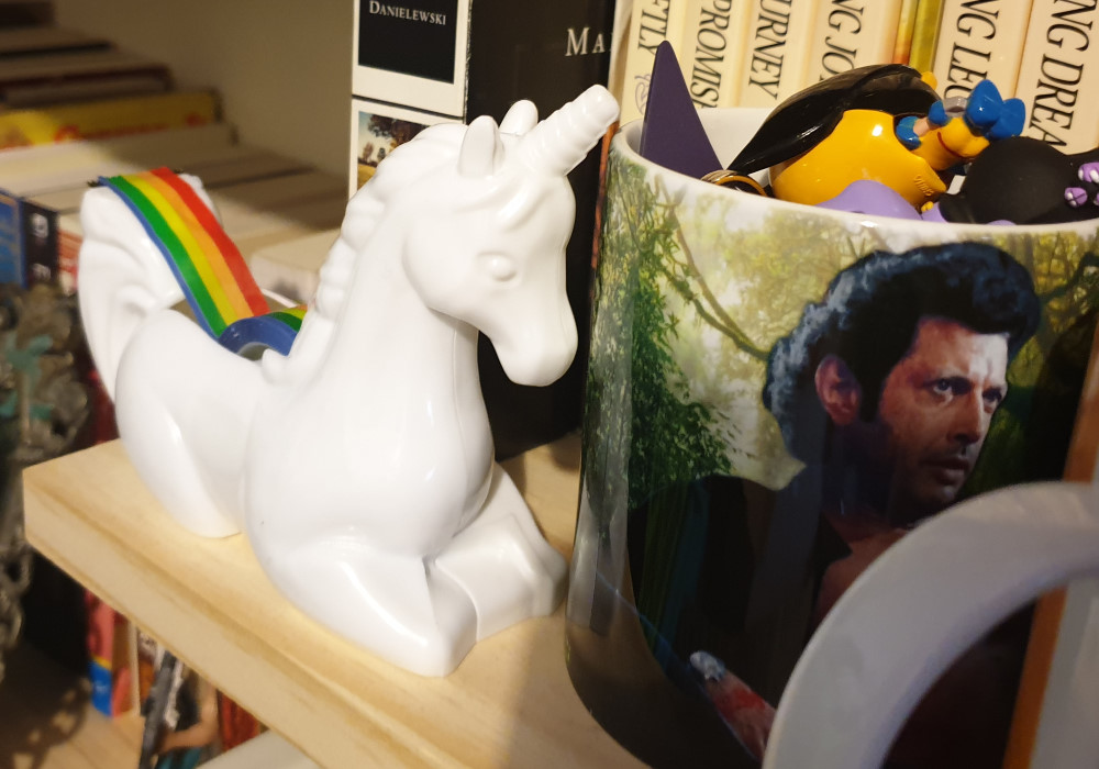 A tape dispenser in the shape of a unicorn and a mug filled with small keychains