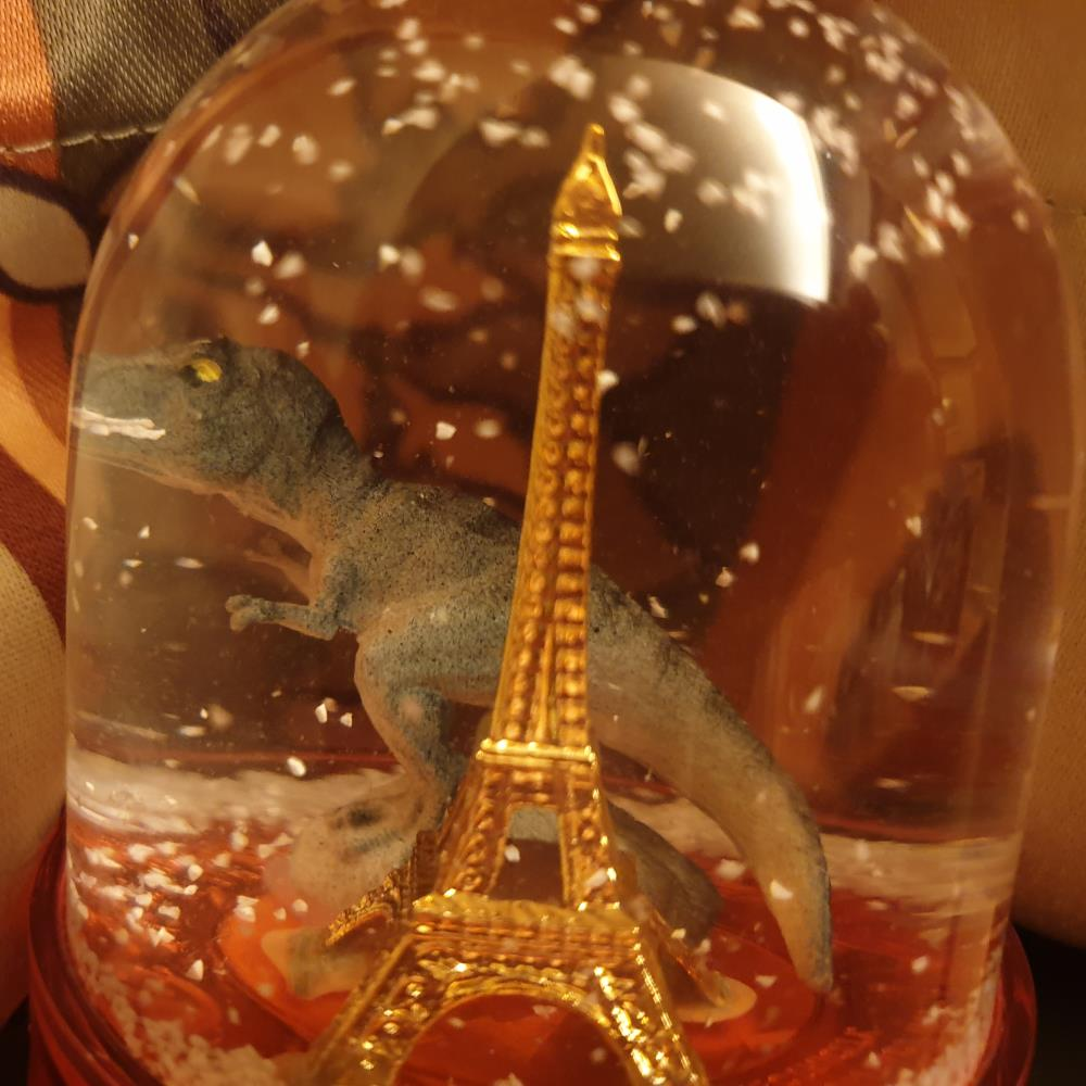A snowglobe with a Tyrannosaurus Rex next to the Eiffel Tower
