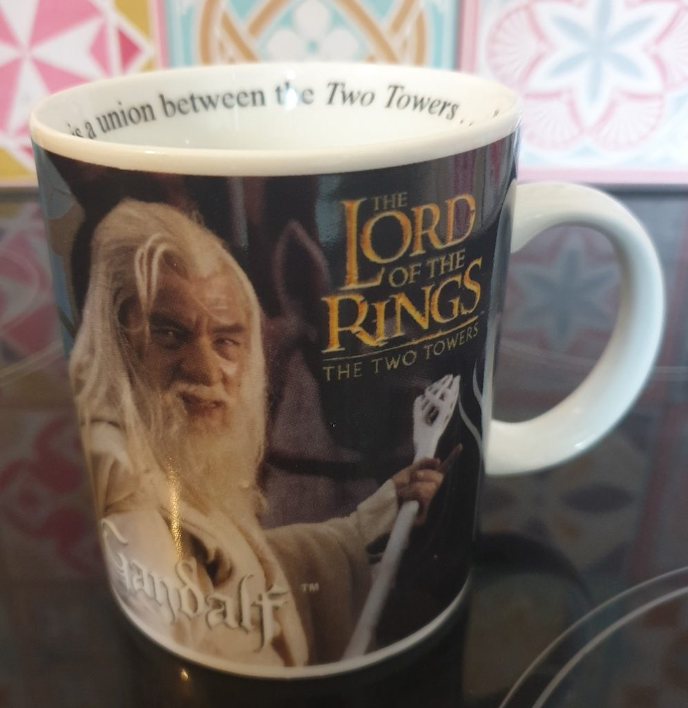 A coffee mug sitting on top of the stove, with a picture of Gandalf the White and the Lord of the Rings: The Two Towers logo on it.